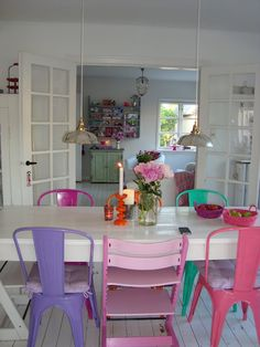 I had this idea for my house- white table, Key West colored chairs  Looks good with white walls.