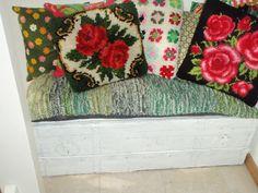 Oude kist in hal met daarin ale sjaals en mutsen. Op de kist liggen allemaal gezellige kussens die met mooi weer op de bank in de tuin liggen.