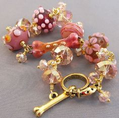 Handmade dog lover bracelet in raspberry pink and gold.  Flamed copper dog bone, artisan lampwork and rose crystal beads.  Dog collar and bone toggle clasp.  For Love of a Dog Jewelry