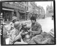 This Nazi soldier, forced to fight for Hilter after his capture as a member of the Russian army, tells American correspondents of his experiences in La Haye-du-Puits while that village was under american shelling left to right are : Pfc Francis Leu, New-York, New-York, John Prince, London Times correspondent, and Philip Grune, London Evening Standard correspondent, France. 11/07/44