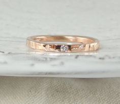 This ring is made of solid recycled 14k Gold which I hammered to give it a textured finish and character. The inside of the ring band is smooth and polished for beauty and comfort.  Measurements approximately 2mm wide x 1.5mm thick. Diamond Measures 1.5-1.7 mm in diameter  *Gold Types available:14k Rose Gold, 14k Yellow Gold and 14k White Gold   Diamond Info: diamond used is a natural certified conflict free diamond.  Eco Friendly and Sustainable: This ring is eco friendly and made from…