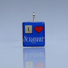 "I Love Scrabble: Wooden Scrabble tile pendant by Scrabble Chick. $8.00.Scrabble tile charm approx. 3/4"" square. Graphic image and embedded metal charm are sealed with a high gloss epoxy resin. Each pendant has a unobstructed letter on back. You may request a special initial . This sale is for one charm. $8.00"