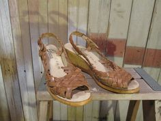 70s heels, with a tall wedge heel and a peep toe, these sandals are made of woven leather and are the perfect 70s summer shoe. Marked 7B, they are