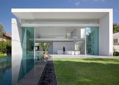 Double-height glass doors slide back to open up an entire facade of this house in Israel by architect Pitsou Kedem.