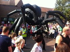 Hire a Walk Around Giant Spider | Halloween Themed Entertainment London |   Walkabout Inflatable Puppet Spider  Arachnobot the spider is a giant walkabout act wich roams the streets looking for prey, or anyone brave enough to say hello!  The 4m high inflatable spider is a fully articulated puppet controlled by a single puppeteer.