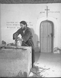 Civil War/Greece  An Orthodox priest getting water from a well.Location:Louzesti, Greece  Date taken:December 1947  Photographer:John Phillips