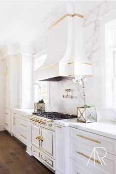White and gold kitchen features white cabinets adorned with long gold pulls paired with Silestone countertops and backsplash that resemble white marble. home decor and interior decorating ideas. Kitchen Ikea, Kitchen Hoods, New Kitchen, Kitchen Interior, Kitchen Decor, Kitchen Cabinets, Brass Kitchen, Kitchen White, Kitchen Modern