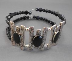 There are three silver metal sliders with black onyx beads and small black onyx beads on memory wire on this bracelet. There is no clasp and it fits most any size wrist.