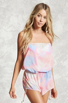 A woven cover-up romper featuring an allover tie-dye print, a strapless design, elasticized neckline and waist, and drawstring sides with hanging self-tying straps with high-polish ends.