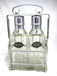 How groovy is this liquor decanter set?!!  They're kinda like liquor snow cone dispensers :)  lol  One of the labels says RYE --- Who drinks Rye anymore?!!  Gotta love these... Vintage Art Deco Tantalus Liquor Decanter Set Pressed Glass in Chrome Caddy