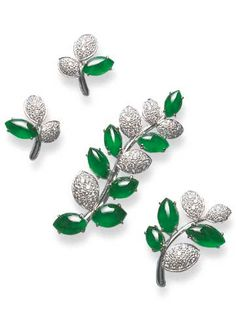 A SET OF JADEITE AND DIAMOND JEWELLERY  Comprising two foliate brooches, each with navette-shaped jadeite cabochons, of very good translucenct brilliant emerald green material and pavé-set diamond leaves; and a pair of earrings en suite, mounted in 18k white gold.