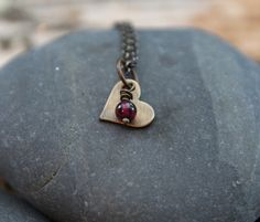 The perfect daily reminder that you are loved. This little heart necklace includes a raw brass heart that has been aged by hand and a small garnet gemstone that is a deep wine, burgundy color.