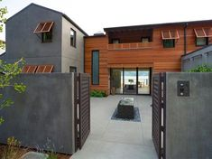 A pair of latticed doors opens onto a modern courtyard with a water feature. Cool gray stucco blends with warm wood siding, offering balance and giving a hint at the home's modern interiors. Stucco Siding, Stucco Homes, Stucco Exterior, Wood Siding, Exterior House Colors, Exterior Design, Interior And Exterior, Wood Homes, Exterior Cladding