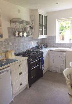 All white work tops and units, blue batik tiles and vintage painted cupboards in my kitchen.