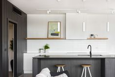 The approach for the interior design was to design a sophisticated coastal style that would connect the outdoors into the internal spaces. The interior concept is three 'black boxes' to float in the space taking the form of the enclosed stair, butlers pantry and island bench. The external cladding colour was brought inside to connect the outdoors to inside seamlessly. Built by Mode Projects to sell, the result was a house that was sold almost instantly.