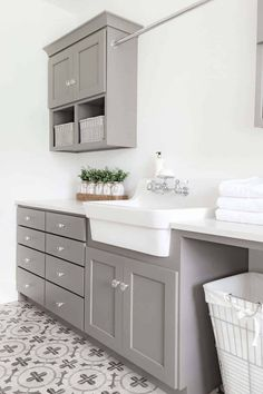 Gray shaker laundry room cabinets with glass knobs surrounding a white apron sink topped with white quartz countertops. Gray shaker laundry room cabinets with glass knobs surrounding a white apron sink topped with white quartz countertops. Grey Laundry Rooms, Farmhouse Laundry Room, Farmhouse Kitchen Cabinets, Laundry Room Design, Kitchen Cabinet Doors, Farmhouse Furniture, Kitchen Paint, Kitchen Decor, Country Farmhouse