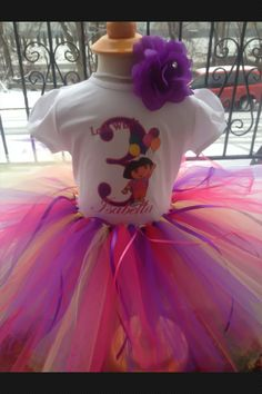 Custom made Dora tutu outfit!   Tutu is made with yards upon yards of soft tulle in fuchsia, purple and yellow. Adorned with ribbons all around.  Custom T-shirt with Dora character, name and age!     *headband will be included based on availability* You will always receive a free headband with yo...