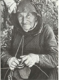 Here's a Greek woman knitting with the yarn around her neck and a safety pin on her shirt for tension.
