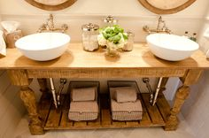 Gorgeous master bathroom design with balustrade salvaged wood bathroom vanity, round vessel sinks, wire baskets, glossy subway tiles backsplash, polished nickel wall-mount faucets, linen tissue box, glass canisters and wood convex round mirrors.