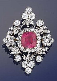A Belle Époque ruby and diamond brooch. The central square cushion shaped ruby in millegrain setting with old brilliant-cut diamond border and openwork floral design lozenge shaped surround with trefoil or flowerhead cluster quarters, set throughout with old brilliant and old-cut diamonds, circa 1905. #BelleEpoque #antique #brooch