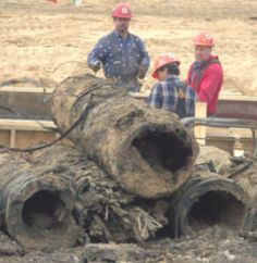 Eight-foot long sections of hollowed out wooden waterlines, beleived to be about 130 years old, made by the Michigan Pipe Works, are shown after being dug up at the new library site at Center and Jefferson.