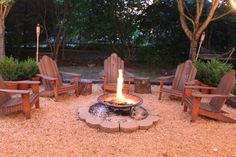 lined with RR ties, use cut logs/stumps for side tables, cheap fire pit lined with cheap stone, I would use sand for base, chairs or benches, a few tiki torches... fairly cheap summer fun, no worries about spills