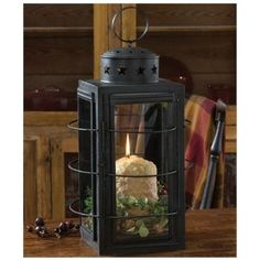 Three Ring Lantern is an adapted larger version of a mid 19th-century black distressed tin and glass lantern with strap handle and wire guards. It includes popular cut-out stars to allow for ventilation. A beautiful accent piece for farmhouse, country, rustic, vintage, or cottage decor.