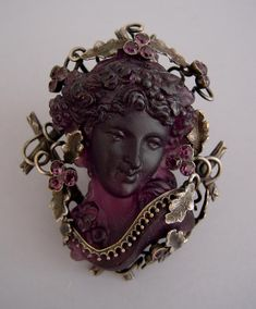 """CAMEO style purple glass pate de verre brooch in an intricate and artistic silver 2-1/2"""" setting, circa 1900. The setting is fashioned so that it cleverly holds the high-relief cameo without prongs."""