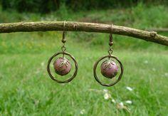 Boucles d'oreilles composées d'une perle de Rhodonite entourée de coupelles et d'un anneau torsadé couleur bronze. S'attachent par un crochet d'oreille garanti sans ni…