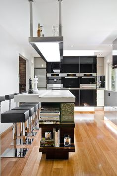 A Contemporary Kitchen in Australia by Darren James  Light over island & display shelves at end of cabinets