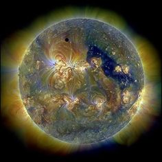 Venus in front of the Sun: What you're seeing is a strange solar eclipse, in which Venus passed in front of the sun. The tiny black dot on the top lefthand side is Venus. The giant psychedelic fireball is the sun, imaged in three colors of ultraviolet light.