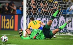 Quiet evening: Germany goalkeeper Manuel Neuer gets down low to deny Brazil frontman Oscar...