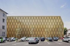 French practice Antonio Virga Architecte has used perforated brickwork and gold metal to wrap a cinema building in Cahors, France, which filters light onto the surrounding public square at night.