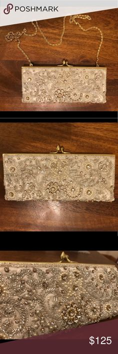 """Moyna Ivory Crystal Beaded Clutch (Used Once) Beads, crystals and pearls create a stunning and elegant motif atop this glamorous clutch. It fits an iPhone, tissue, lip gloss, and floss. There's a small compact mirror included and has hidden 20"""" gold chain strap. It's 4"""" in height, 8.5"""" in width and 1"""" deep. It's handmade by Moyna.   Only used once during my wedding in 2017 and is in excellent condition. Original owner. Will include dust bag that came with clutch purchase. Moyna Bags Clutches…"""