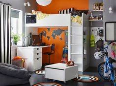 A black, grey, orange and white bedroom for a child in their pre-teens with a white STUVA loft bed with a desk and built in storage.