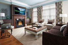 Large Blue Living Room with Tufted Coffee Table containing: Dark Brown Sofa with Stripe Armchair also Geometric Accent Chair plus Varnished Wood Flooring together with Wooden Fireplace Frame with Patterned Window Cover also Square Patterned Rug plus Wall Mount Tv