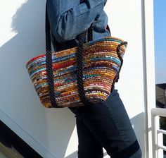 This Vienna Market Basket Bag or tote is wrapped in rich gold, russet and caramel tones. Shades of turquoise and royal blue contrast with its warm tones. Its design is inspired by all the lovely baskets I see when I shop Vienna's outdoor markets.    I hand wrapped over 100 feet of cotton rope with new and upcycled fabrics then machine stitched the wrapped rope into the bag shape. I finished one end with an elongated swirl design in black and white polka dot fabric. This matches the handles…