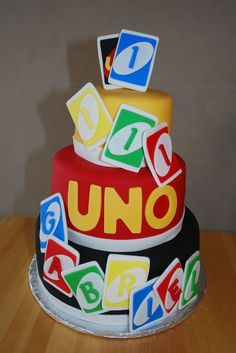 The first birthday theme was UNO.  It is a 3 tiered chocolate cake / chocolate mousse filling / chocolate frosting.  The cake is covered with fondant and the UNO cards are made of fondant.
