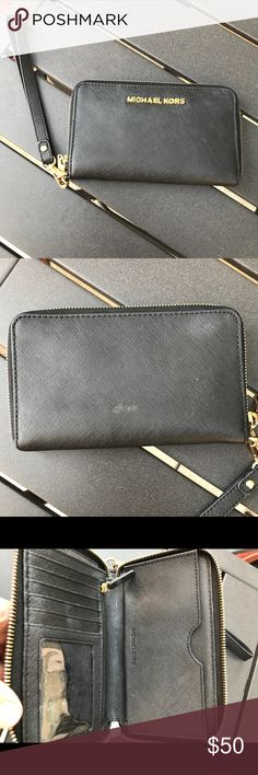 """Michael Kors black leather """"jet set"""" wristlet This piece is in great condition minus a small stain/spot on the back (pictured) no other damage. Lightly used. This sleek case is the perfect all-in-one accessory. It features a dedicated pocket for your phone and a wealth of card slots for easy organization. A must-have when traveling, tuck it into your everyday carryall for effortless elegance. • 100% Saffiano Leather  • Gold-Tone Hardware  • 8.5""""W X 4.5""""H X 1""""D  • Handle Drop: 7""""  •…"""