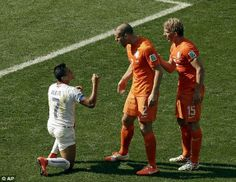 Chile's Alexis Sanchez (7) has words with Holland's Ron Vlaar (2) as Dirk Kuyt (15) looks on