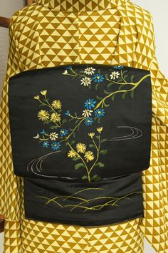 つややかな黒の繻子地に、イングリッシュガーデンを彩るような可憐なお花が刺繍されたロマンチックな名古屋帯です。