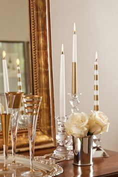 Candles were taped and then spray-painted with gold and glitter-gold paint to add a modern contrast to the fancy serveware and elegant white roses.