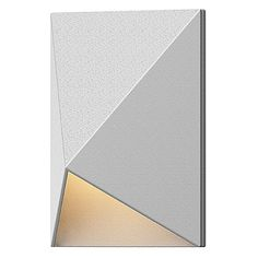 The strong geometric lines of the Triform Compact Indoor/Outdoor LED Wall Sconce bring an architectural element to your outdoor lighting. A triangular shade houses a single LED lamp, casting a subtle down-lit glow. From the Sonneman Inside-Out collection, the compact scale of this wall sconce complements many applications, from outdoor entries to indoor stairways.