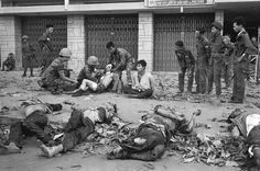 A Viet Cong prisoner sits next to corpses of 11 of his slain fellow guerrillas after a street fight in Saigon-Cholon on February 11, 1968. In the background are Vietnamese Marines that defeated a Viet Cong platoon holed up in the residential area. The prisoner was later taken out for interrogation.