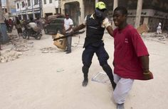 Port au prince ,police officer grabs man. A lot different in other countries compared to protocol and  attire