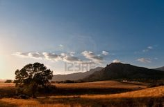 House in the middle of the straw meadow surrounded by mountains bathed in a soft light on a sunny summer day- Horizontal