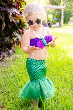 Part of our Mermaid Kisses & Starfish Wishes collection - our Adorable Baby Girl's Little Mermaid Pearl Bikini Tail Swimsuit Bathing Suit - 2 pcs Set - www.crazyaboutboo.com  It is multicolored in shades of shimmery purple and green.  The bikini top is bandeau style and adorned with two purple seashells and white beads; while the bottom is green with a mermaid flutter ruffle tail.  This Mermaid Tail Swimsuit is perfect for Baby's First Birthday, Mermaid Theme Parties, or Halloween costumes.