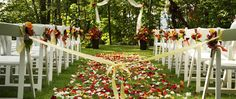 Lisa+Matt: Like chair decoration size is about right, some petals, maybe next to chairs but not whole isle, some yellow flowers with the red/green/white (Matt: get rid of the orange  in this example, and the yellow might work, Lisa: like yellow ribbon keeping guests from trampling isle).  Unsure: Large flower decorations. Dislike lace on arch.