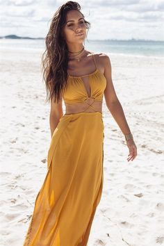 Elegant and bohemian vibes blended together in the stunning Saffron Tie Maxi. This irresistible maxi is made from a textured lightweight fabric in a saffron hue. It features a halter style neck, cutout at bust and waist, cross strap feature at waist, exposed back with tie details and dramatic splits at sides. Complete the look with metallic gold strappy heels. Exclusively designed by Sabo Skirt.
