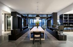 Inside this modern penthouse, a large white dining table sits below three black pendant lights, and divides different areas of the home. New York Penthouse, Luxury Penthouse, Penthouse Apartment, Luxury Dining Room, Elegant Dining Room, Loft Stil, White Dining Table, Design Moderne, Mid Century House